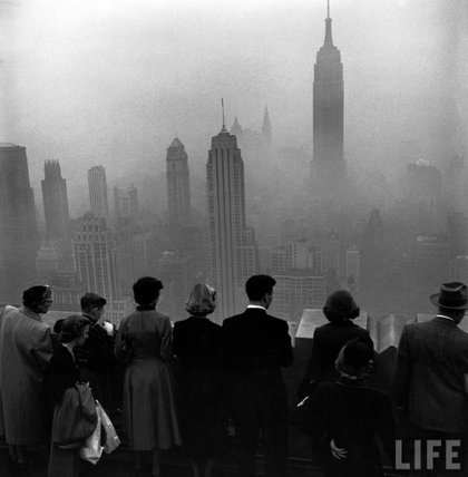 """November 21st, 1953. """"Several people standing on the top of a building looking down into the downtown misty smog that is covering the Empire State and surrounding buildings."""""""