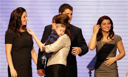 Palin, holding Trig, touches Bristol Palin; Bristol's fiance Levi Johnston stands behind Palin with Willow Palin to the right