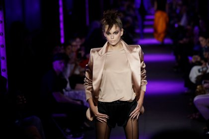 Kaia Gerber in a beige shirt and jacket and black shorts walks the catwalk for Tom Ford