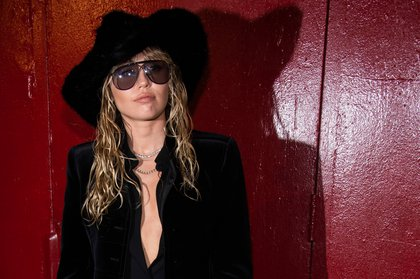 Miley Cyrus, in sunglasses and a hat, poses in front of a red door