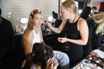 Gigi Hadid gets make-up applied while sitting in a dressing and make-up area in the station, with the tiled wall in the background