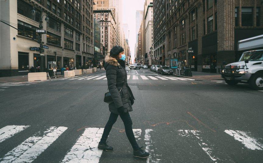 Eine Frau mit einer Maske, die die Straße überquert