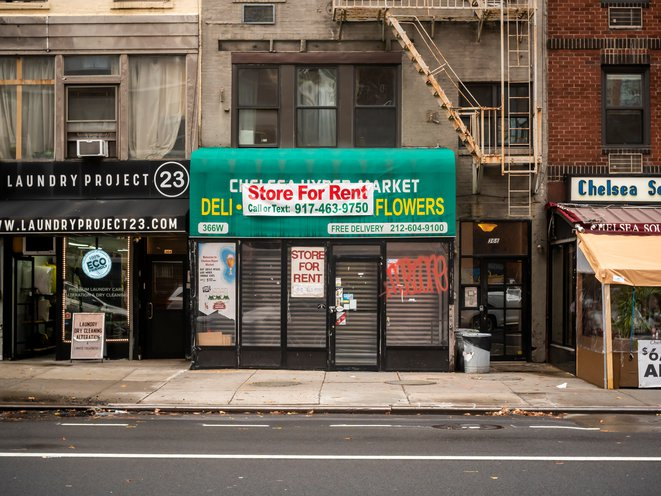 """A bodega is closed, and there's a """"for rent"""" sign on its gate"""