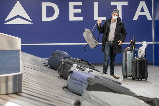 Passenger wearing a face mask collects his luggage at LaGuardia Airport, in New York.
