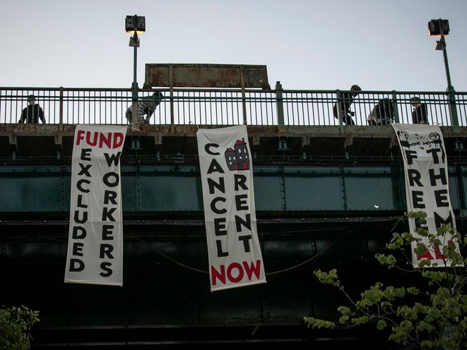 People unfold banners from a subway platform in Queens May 21st, 2020.
