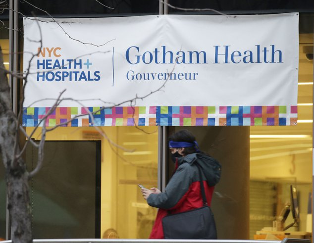 A sign for NYC Health + Hospitals/Gotham Health, one of the sites for coronavirus public vaccinations, hangs above a window at 227 Madison Street in the Lower East Side.