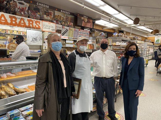 Manhattan BP Brewer, Len Berk, David Zabar, and LG Kathy Hochul stand, wearing masks, in front of Zabar's famed smoked fish counter