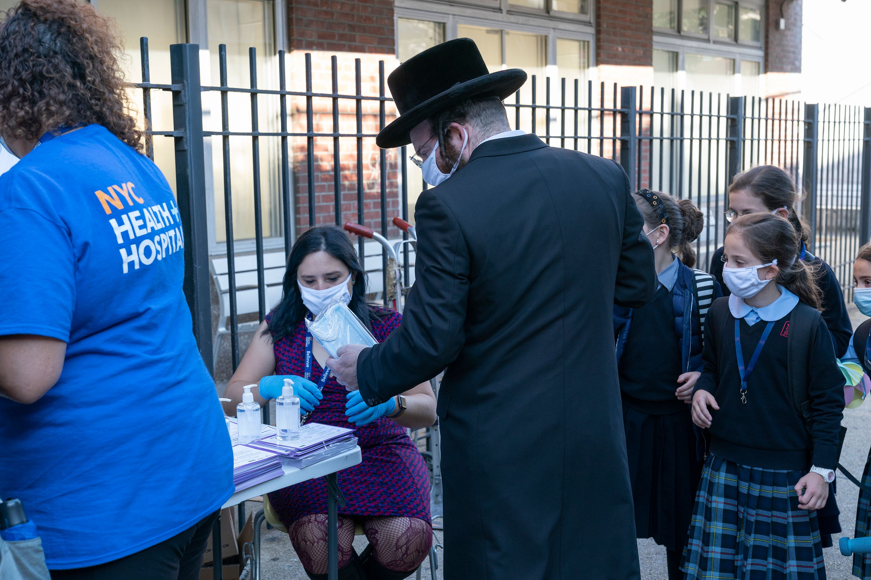 An Orthodox Jewish man in Brooklyn stops by a table manned by the city's Health and Hospitals Corporation informing New Yorkers on the need to get tested.