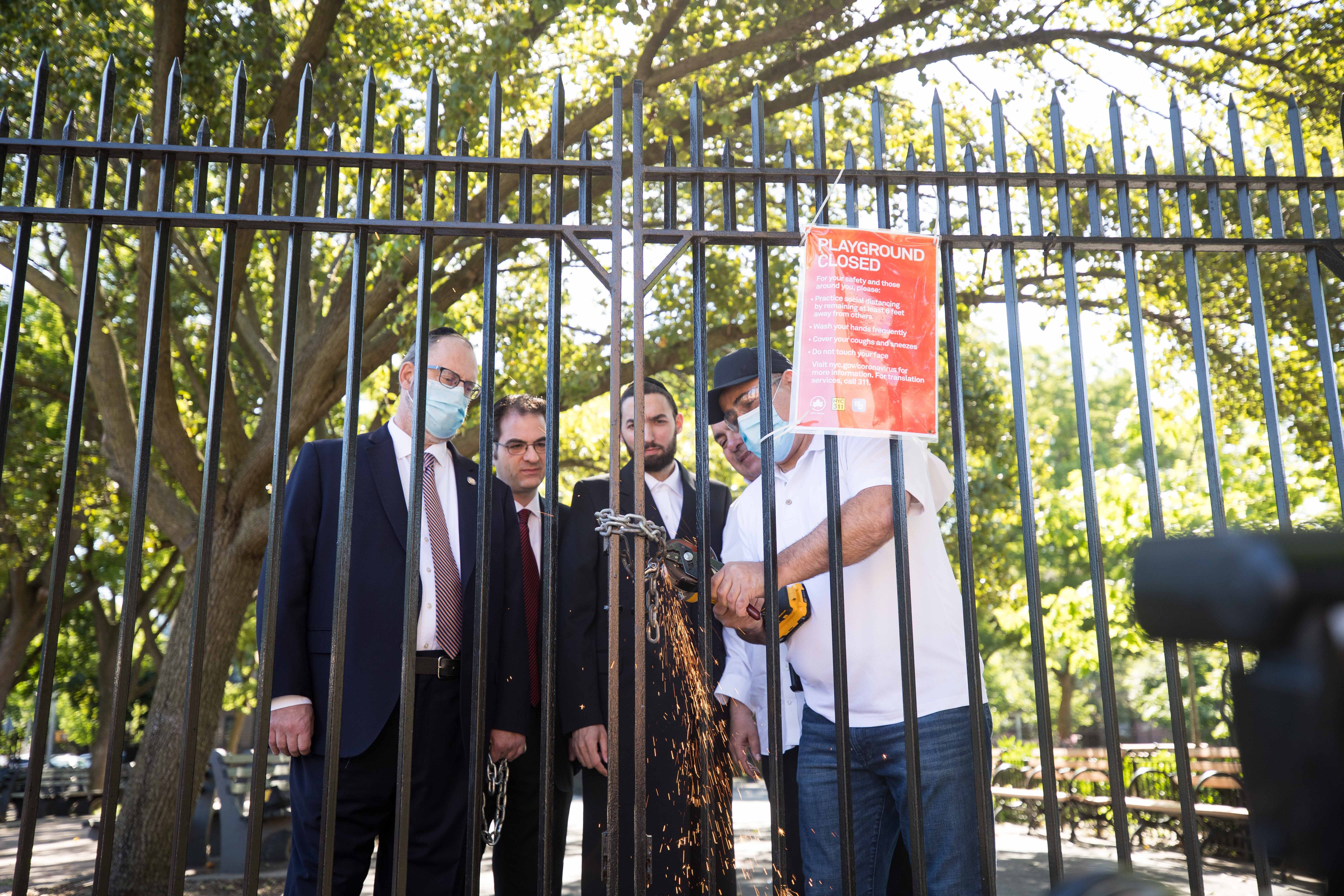 Councilman Kalman Yeger, Assemblyman Simcha Eichenstein, Senator Simcha Felder and an unidentified worker cut the lock at a Brooklyn playground.