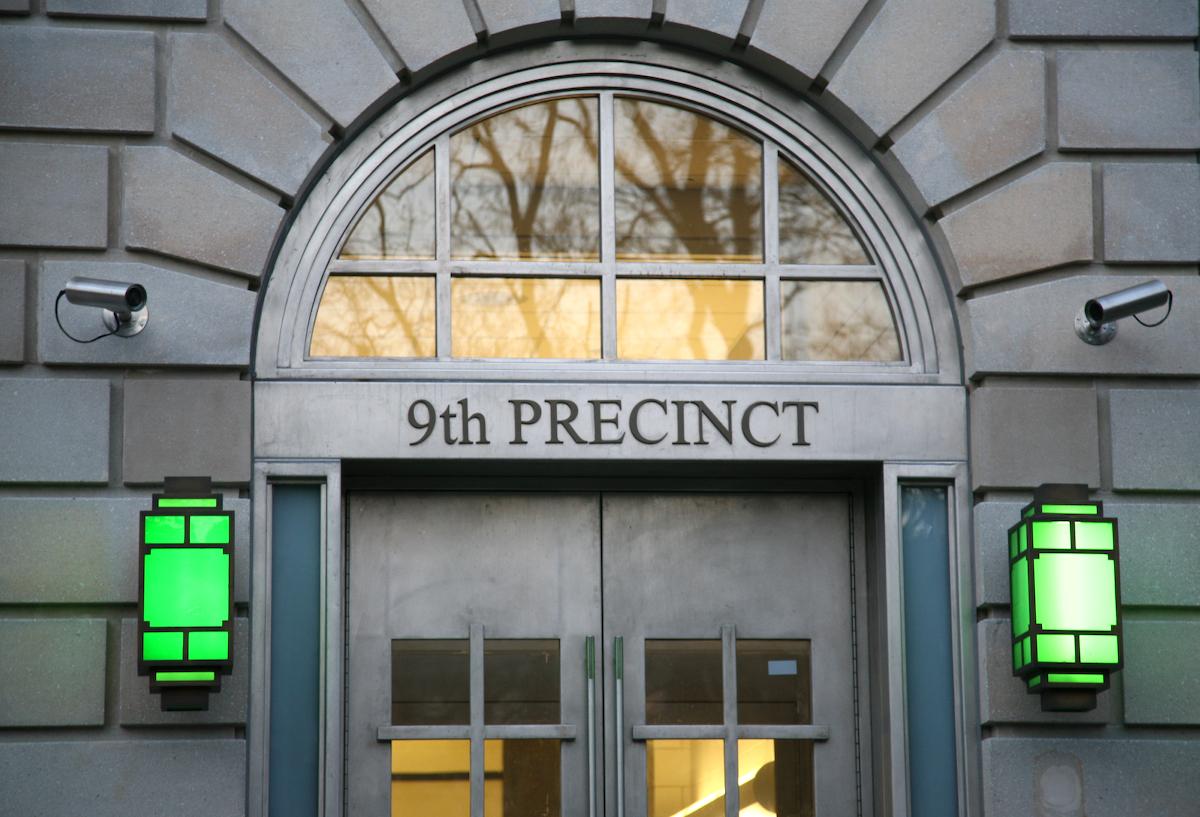 Green lanterns flank the entrance to the grey 9th precinct in Manhattan