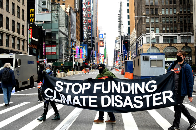 """Activists wearing face masks hold a banner reading """"STOP FUNDING CLIMATE DISASTER"""" in a Manhattan crosswalk."""