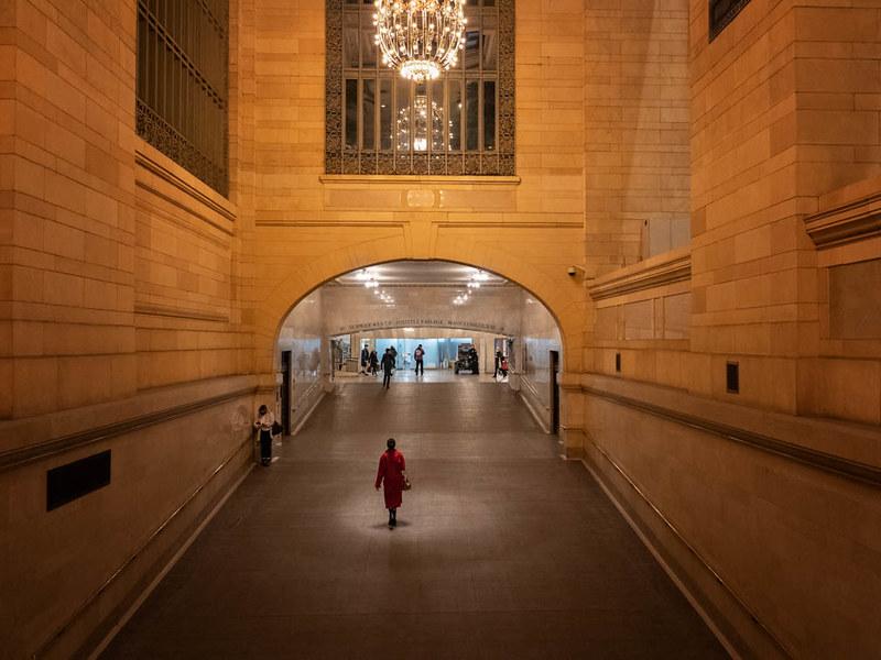 A person walks through a nearly empty corridor inside Grand Central Terminal.