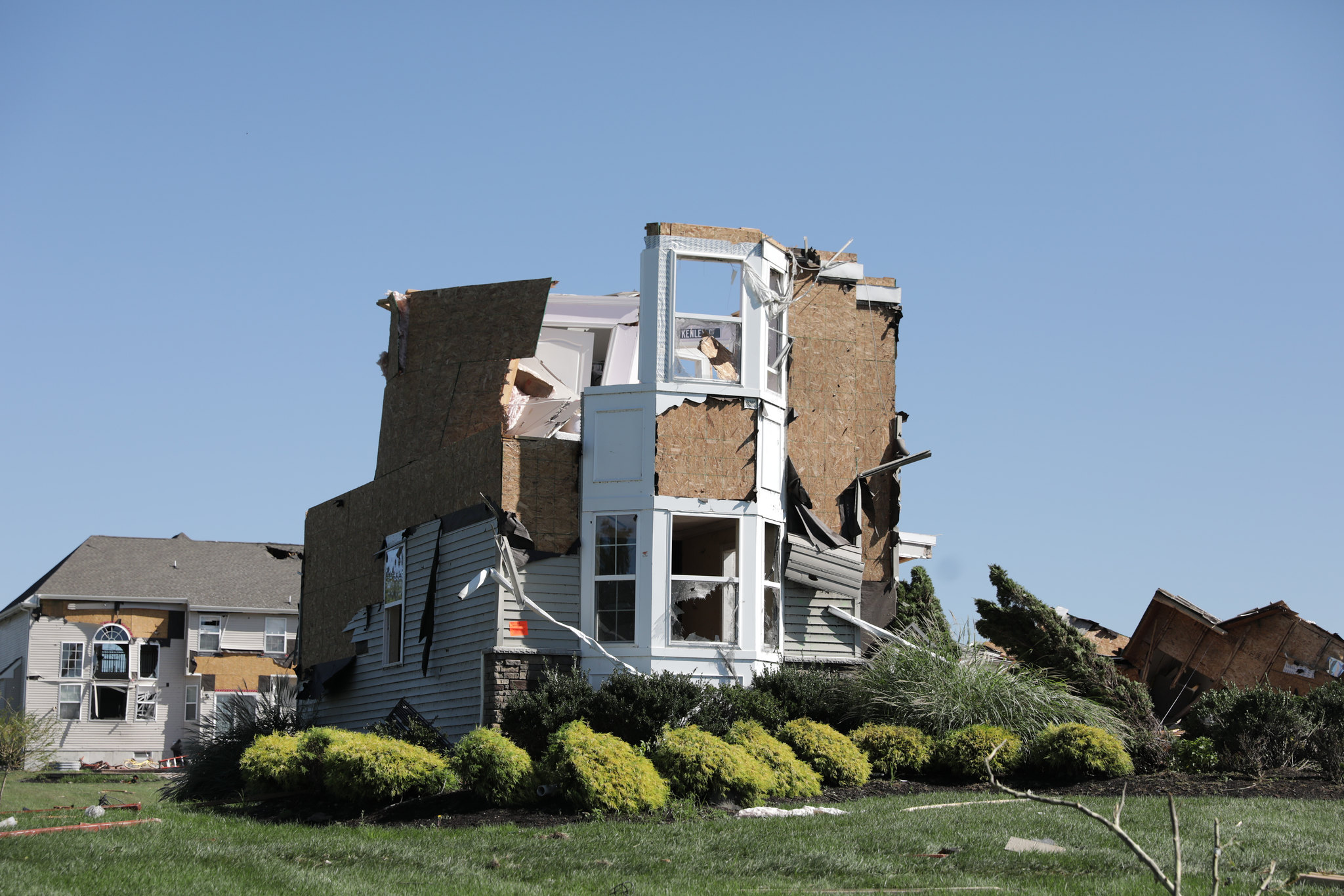 The top floor of a two story house is partly sheared off, with no roof
