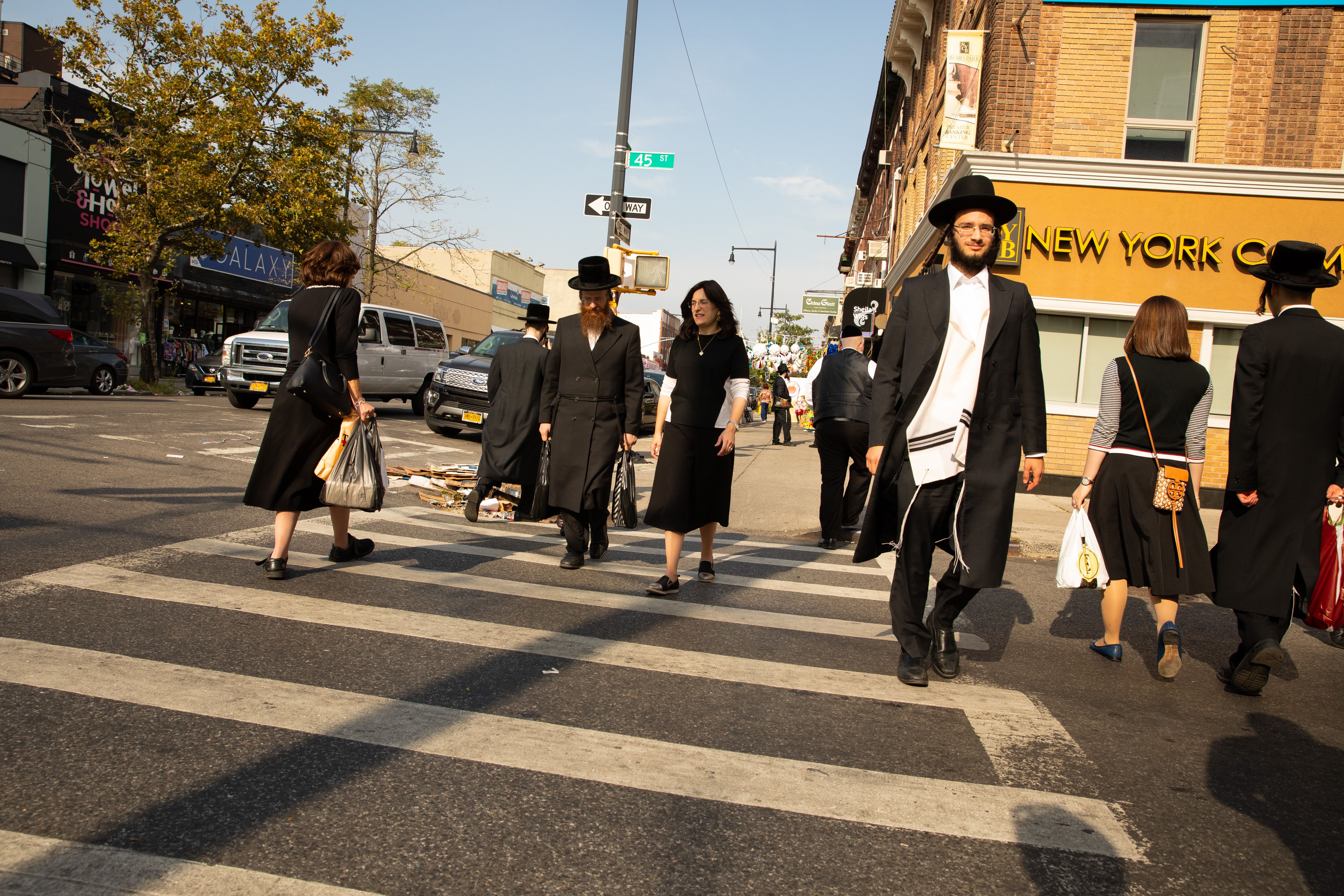 Hasidic New Yorkers without masks cross the street in Borough Park
