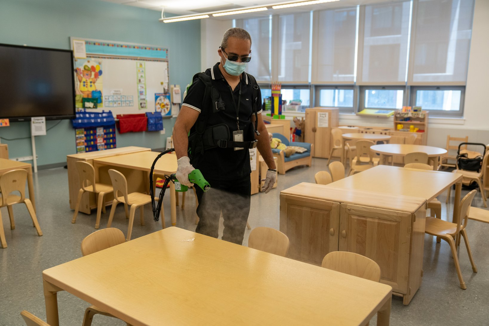 The city Department of Education released this photo of an employee spraying a school desk and cleaning.