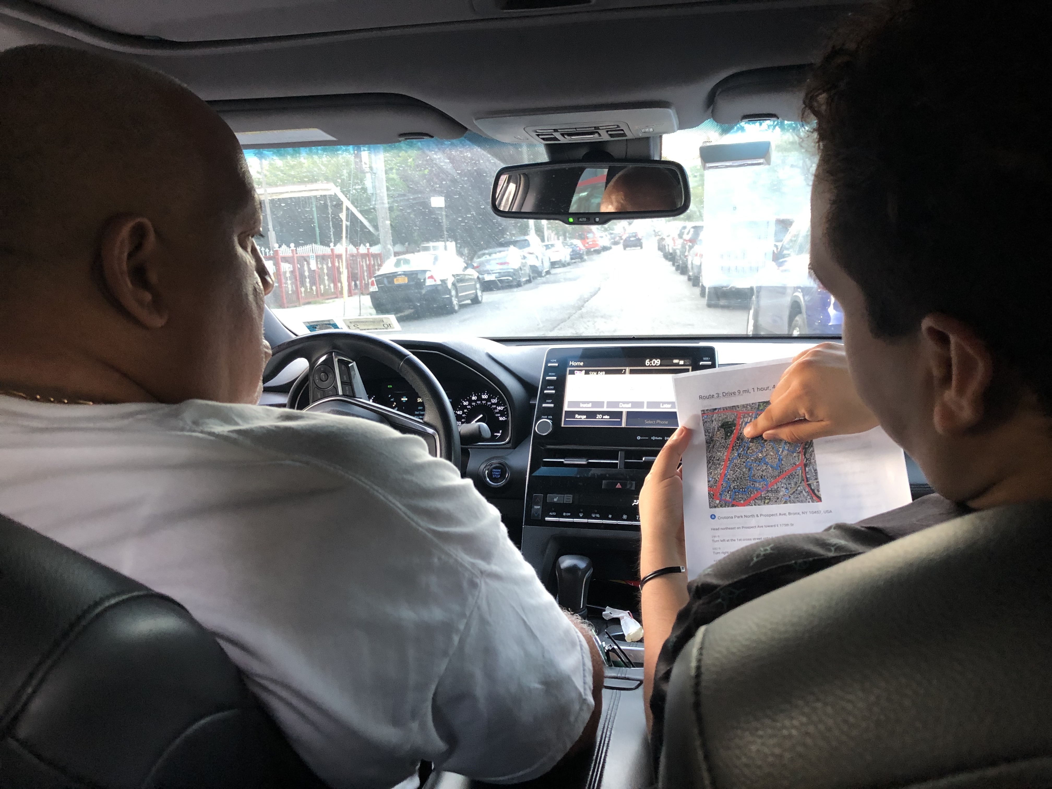 Two men sitting in the driver's and passenger's seat in a car, looking at a map.