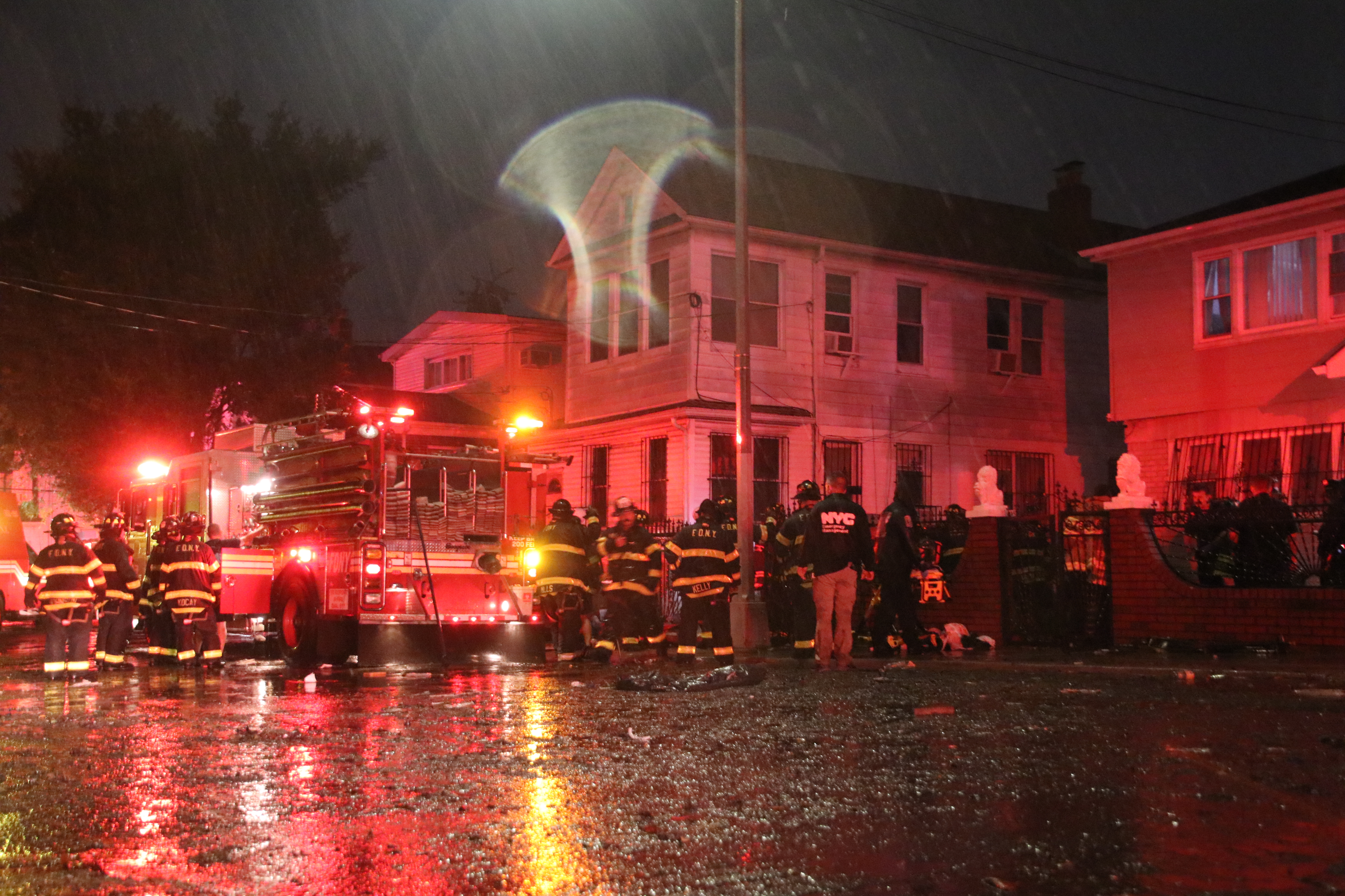 Fire Department members stand outside a white house in queens in the rain