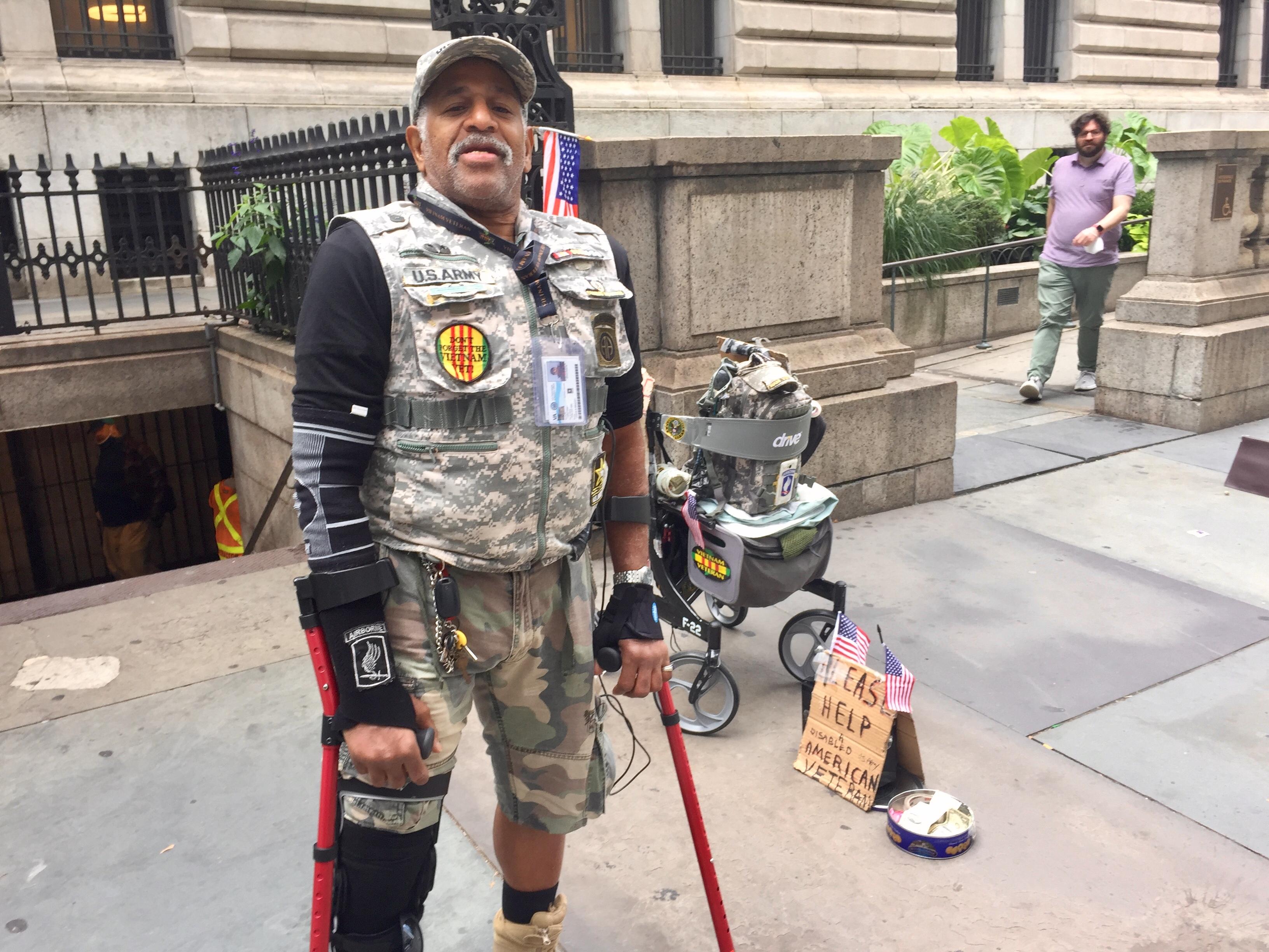 A man wearing a flak jacket and shorts, using crutches