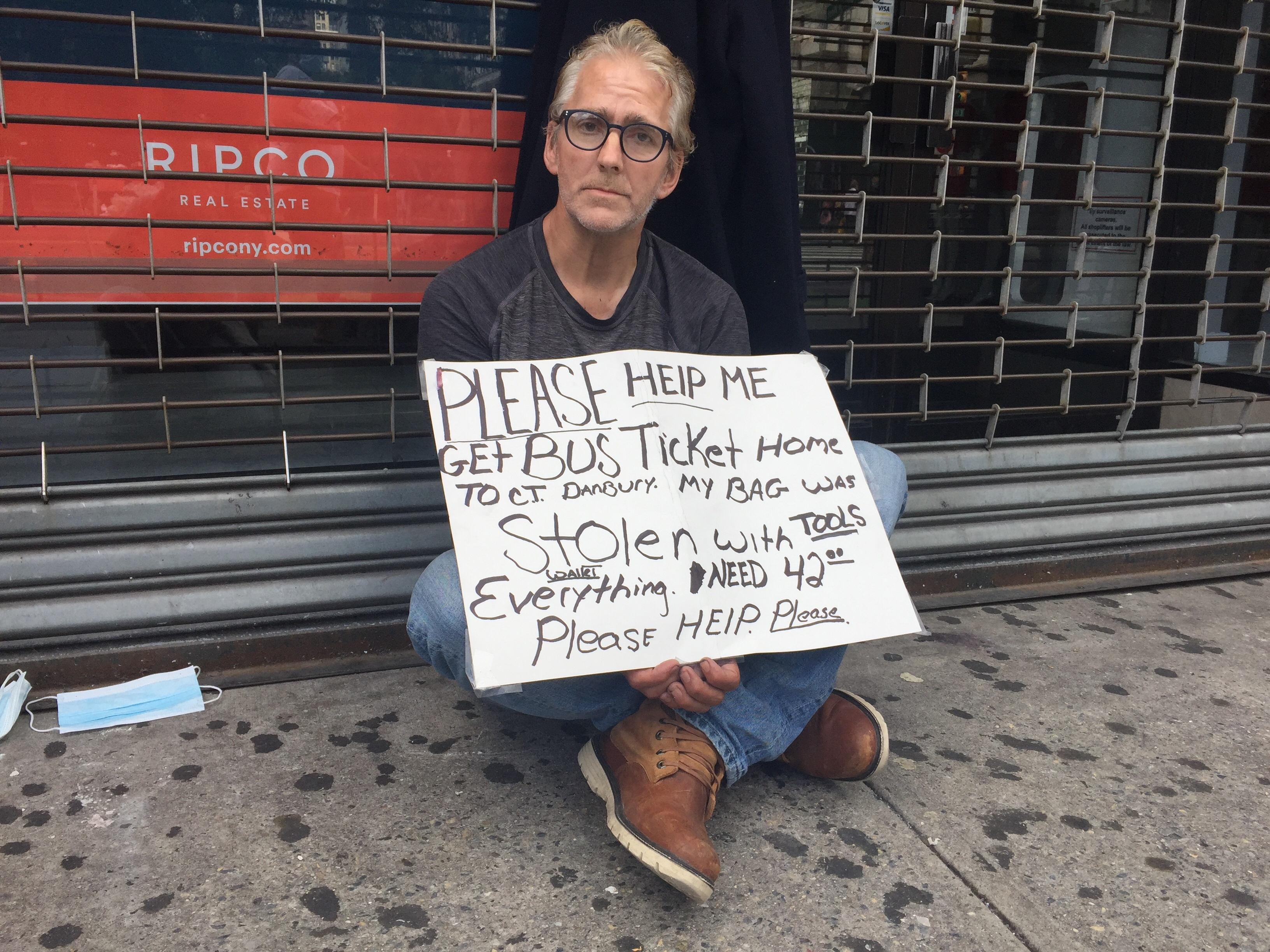 A white man with glasses, with a sign saying he's homeless, sits outside a gated store