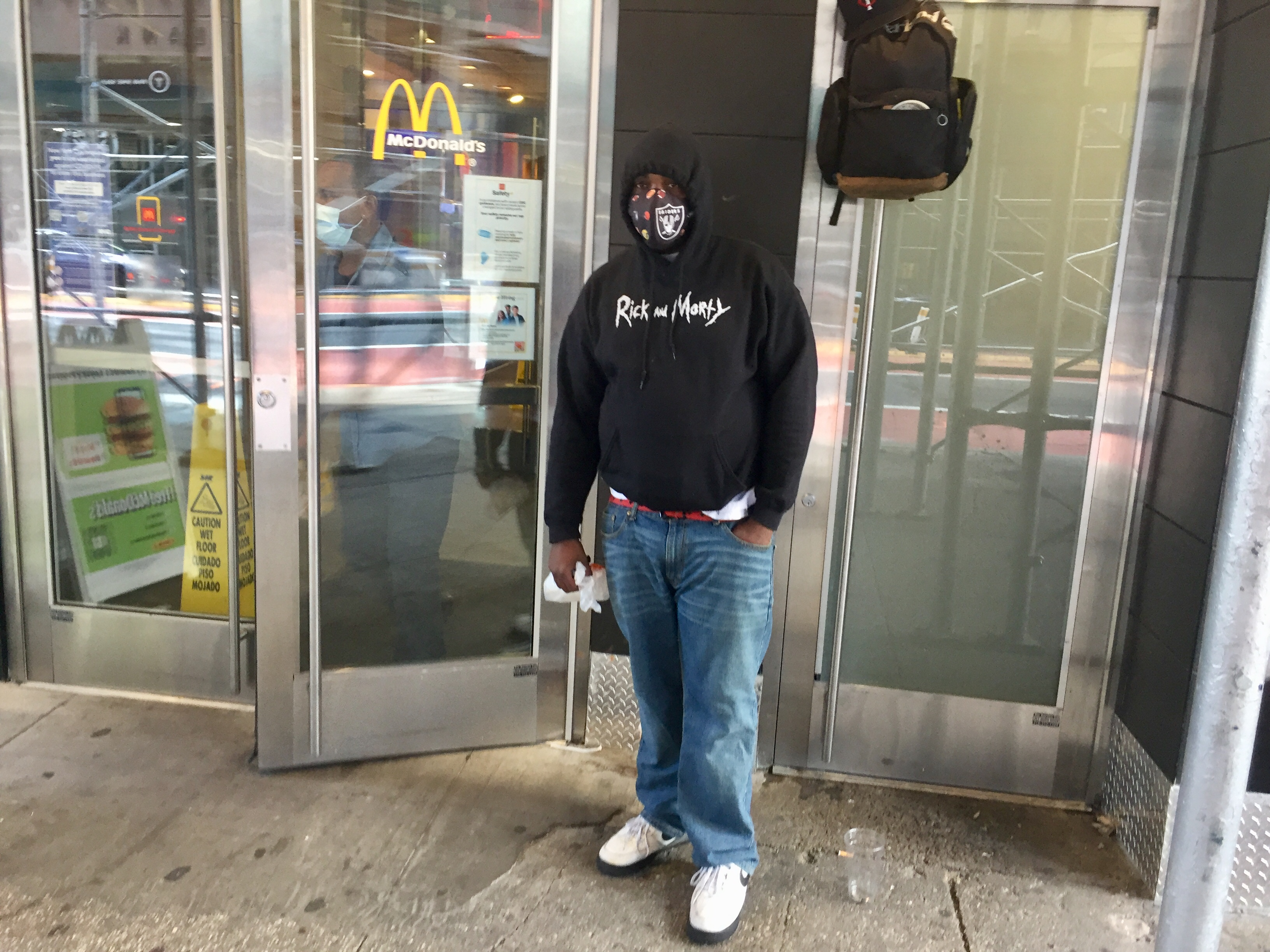 A black man wearing jeans and a hooded sweatshirt wears a mask outside a building