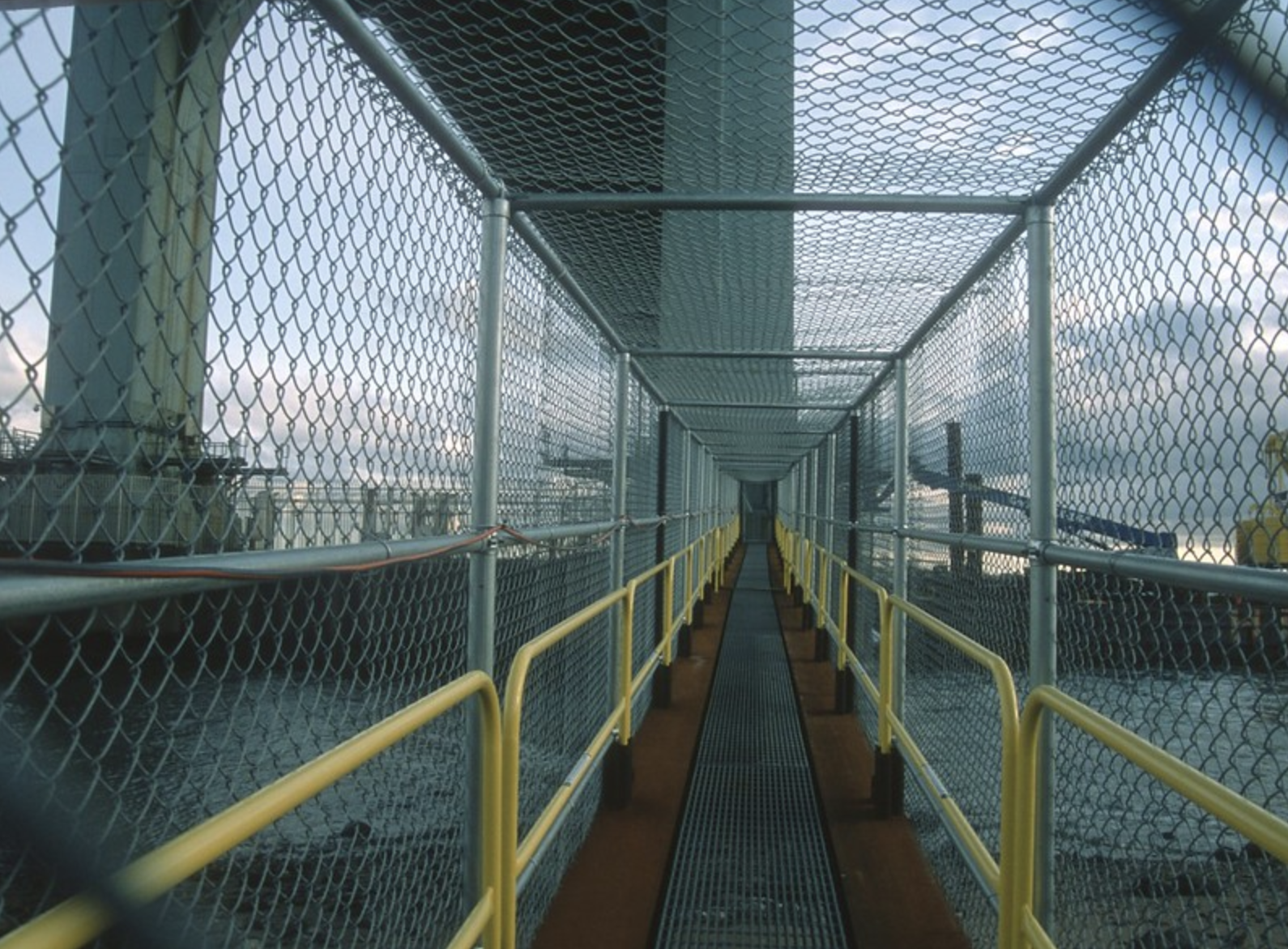 A walkway covered in chain link fencing at the Bronx-Whitestone bridge.