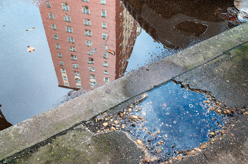 an apartment building seen in the reflection of a puddle