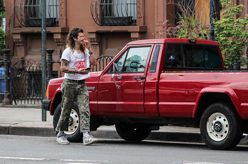 a person with a funny haircut walks in front of a pick-up truck