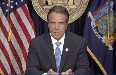 Governor Andrew CUomo in front of state seal and flag