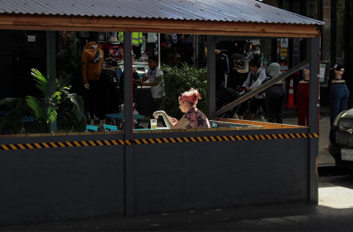عکسی از زنی که بیرون در رستوران Bushwick نشسته است