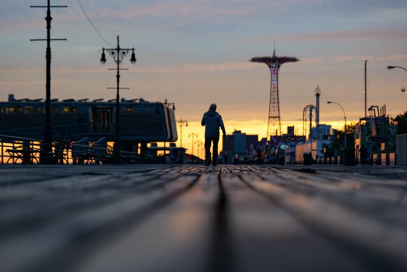 a man walks on the Coney Island boardwalk at sunrise