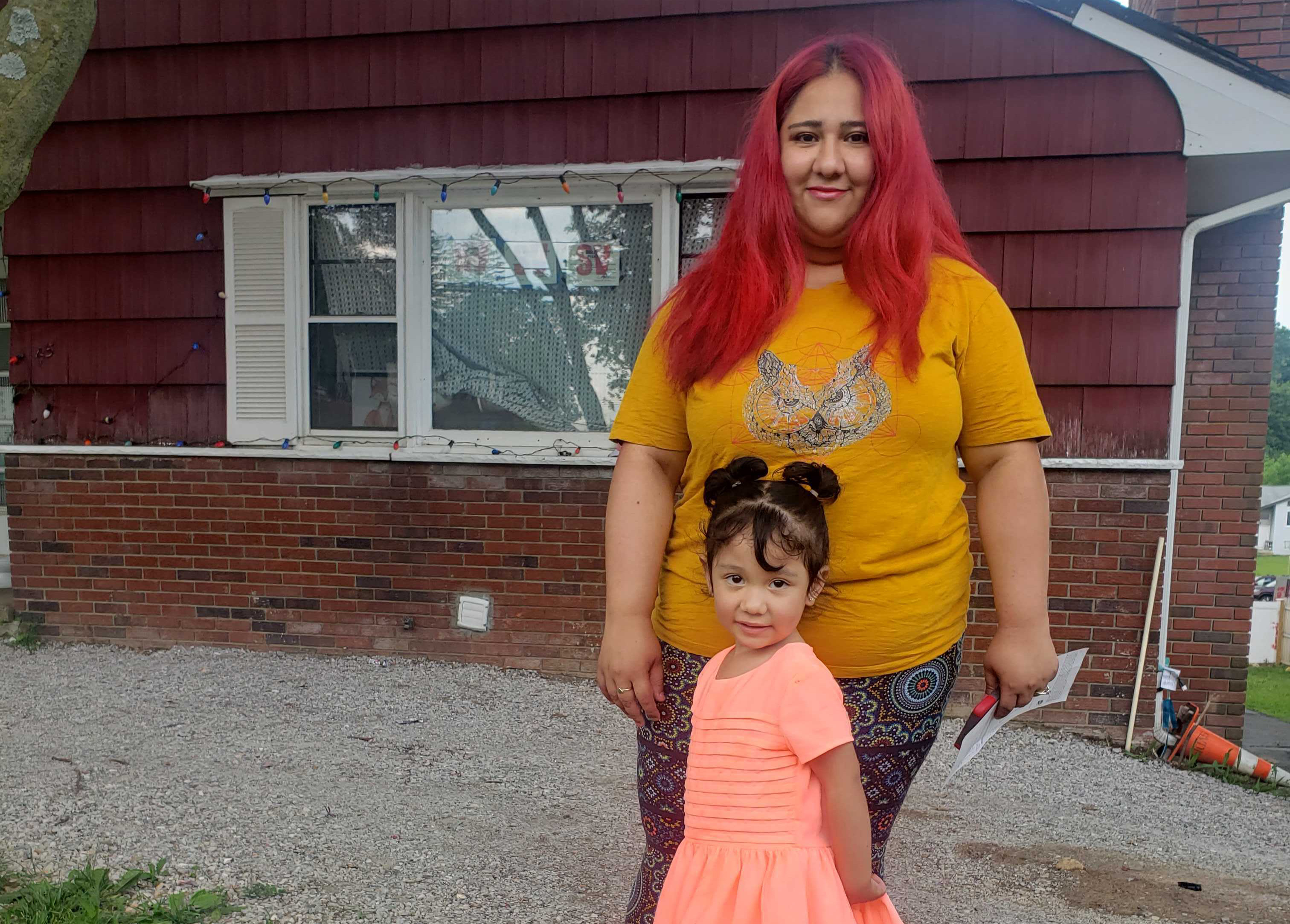 Ana Maeda Gonzalez has red hair and is wearing a yellow t-shirt and her young daughter stands in front of her, wearing a pink dress. They are standing in front of a red house.