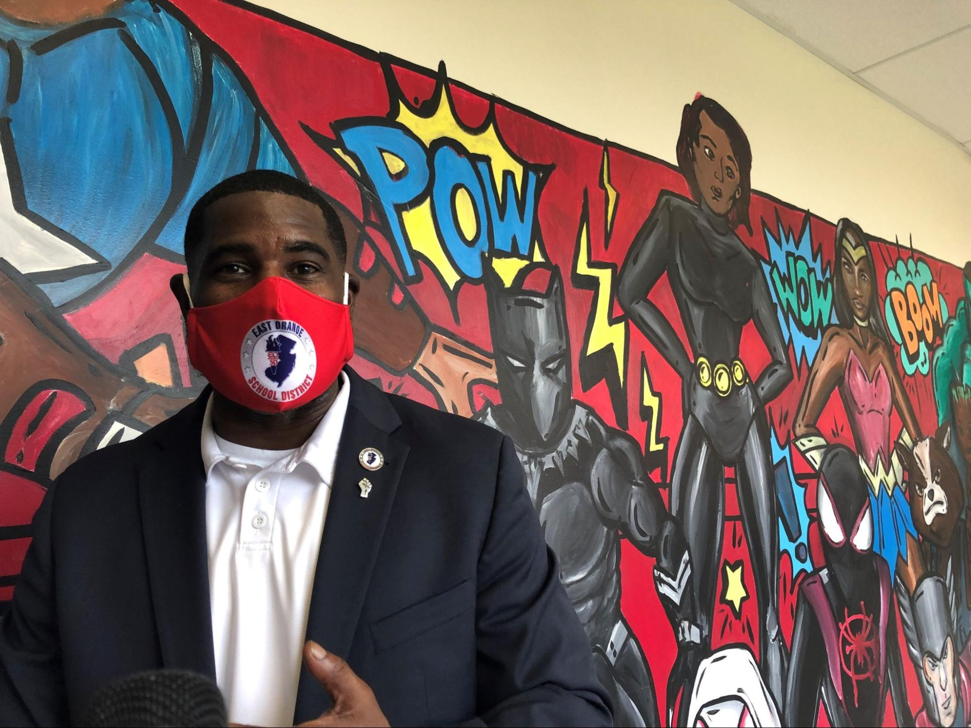 Photograph of East Orange Superintendent AbdulSaleem Hasan wearing a mask in front of a colorful mural