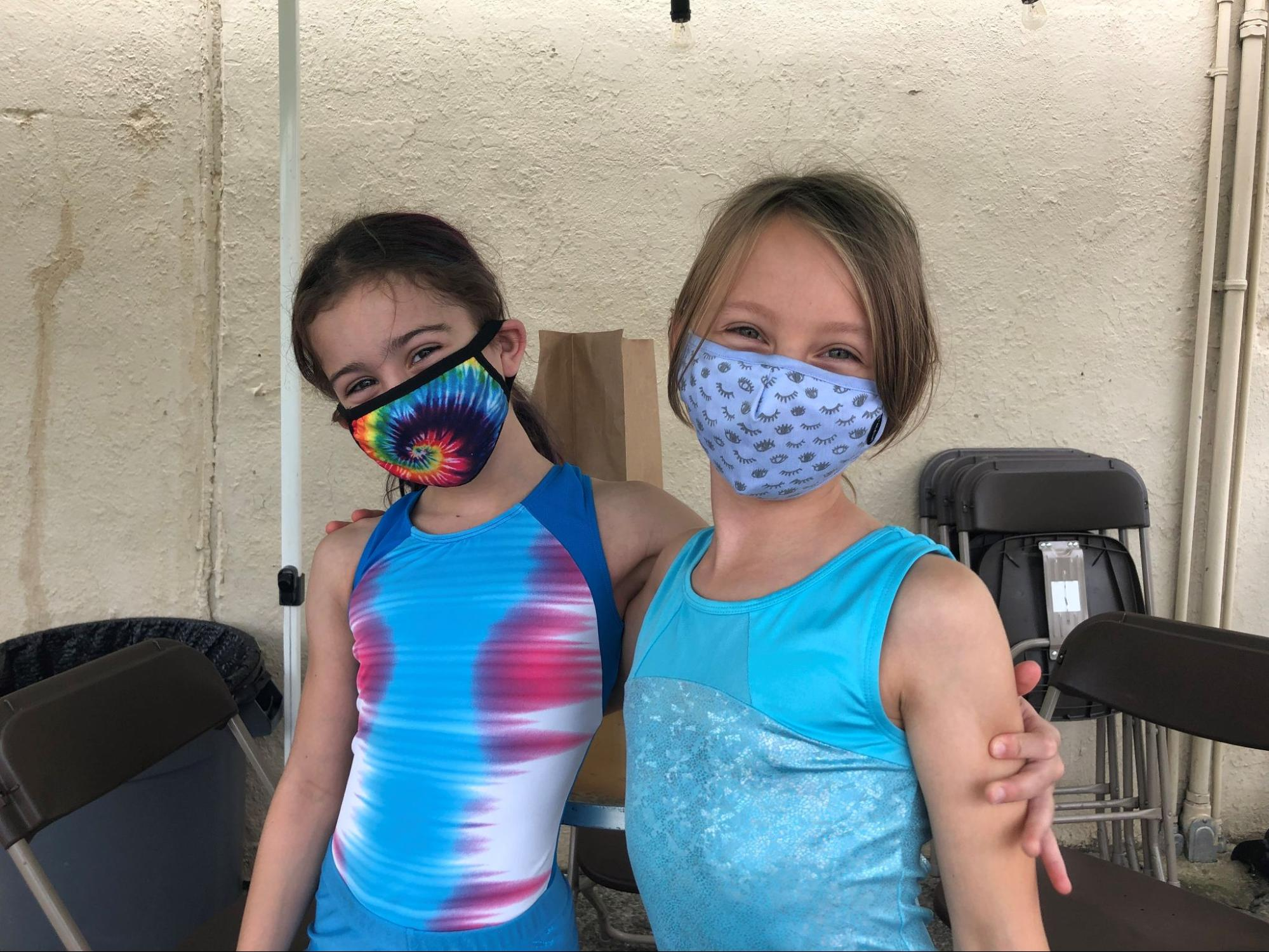 Two young girls wearing masks, with their arms around their shoulders