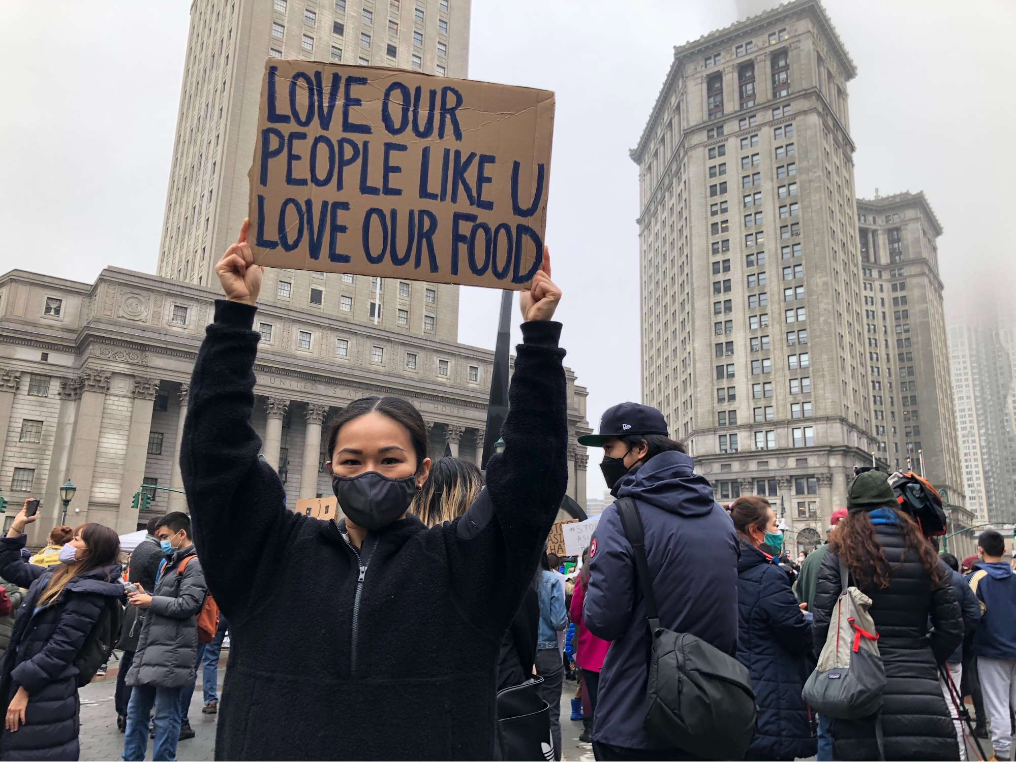 """A woman holds a sign that says """"Love Our People Like U Love Our Food"""""""