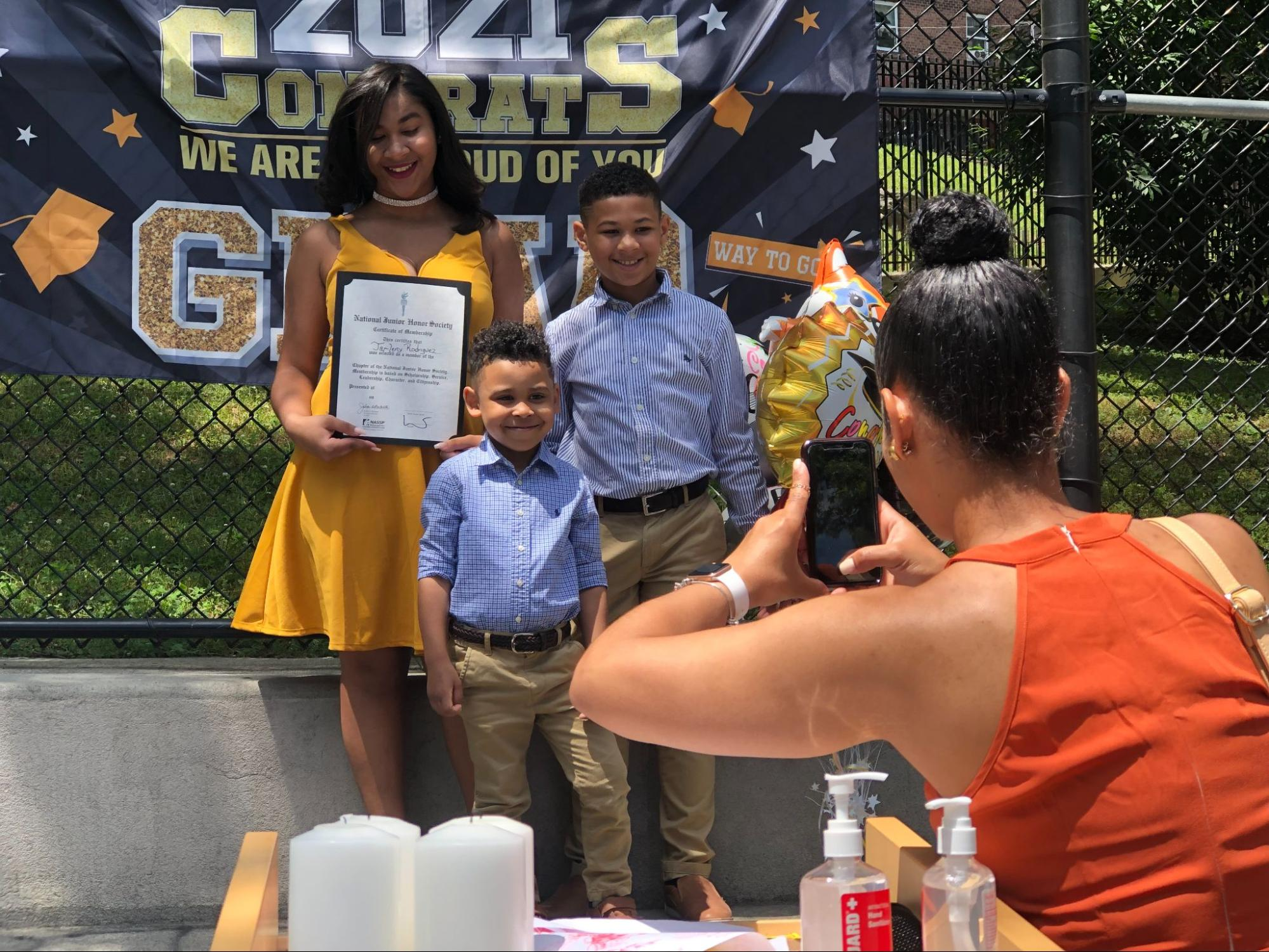 An 8th grader in a yellow dress holds her diploma while her brothers, in blue shirts and slacks, pose with her as their mother takes their picture