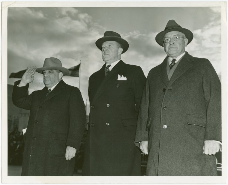 Fiorello Laguardia saluting in a black and white photo with two other men in overcoats