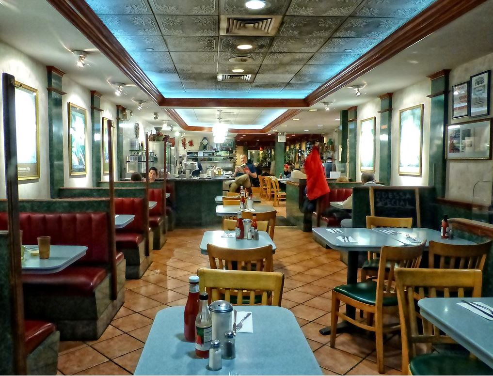 The interior of Odessa diner, showing tables in the middle and booths on the sides, with a counter in the back.