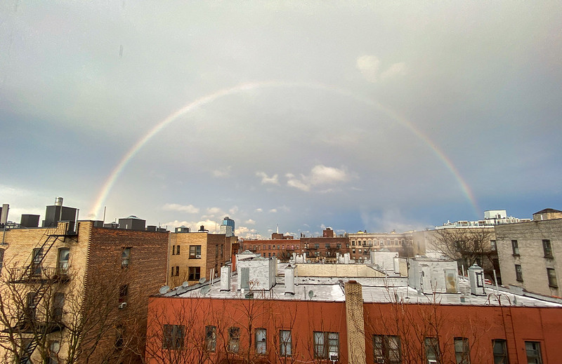 A complete shot of a rainbow over New York City buildings on a drizzly afternoon.