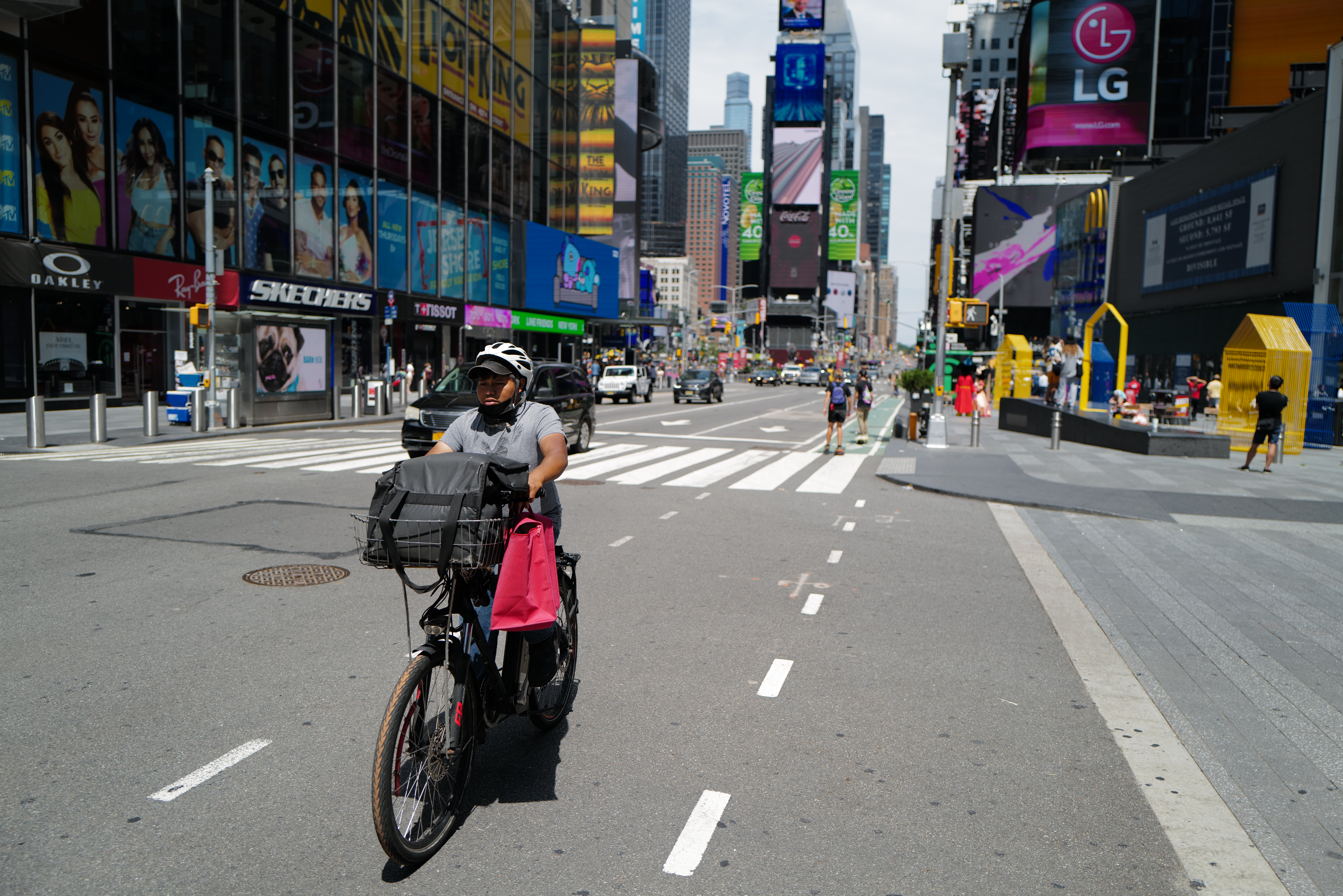 A food delivery person on a bike in Times Square, with a bag of good