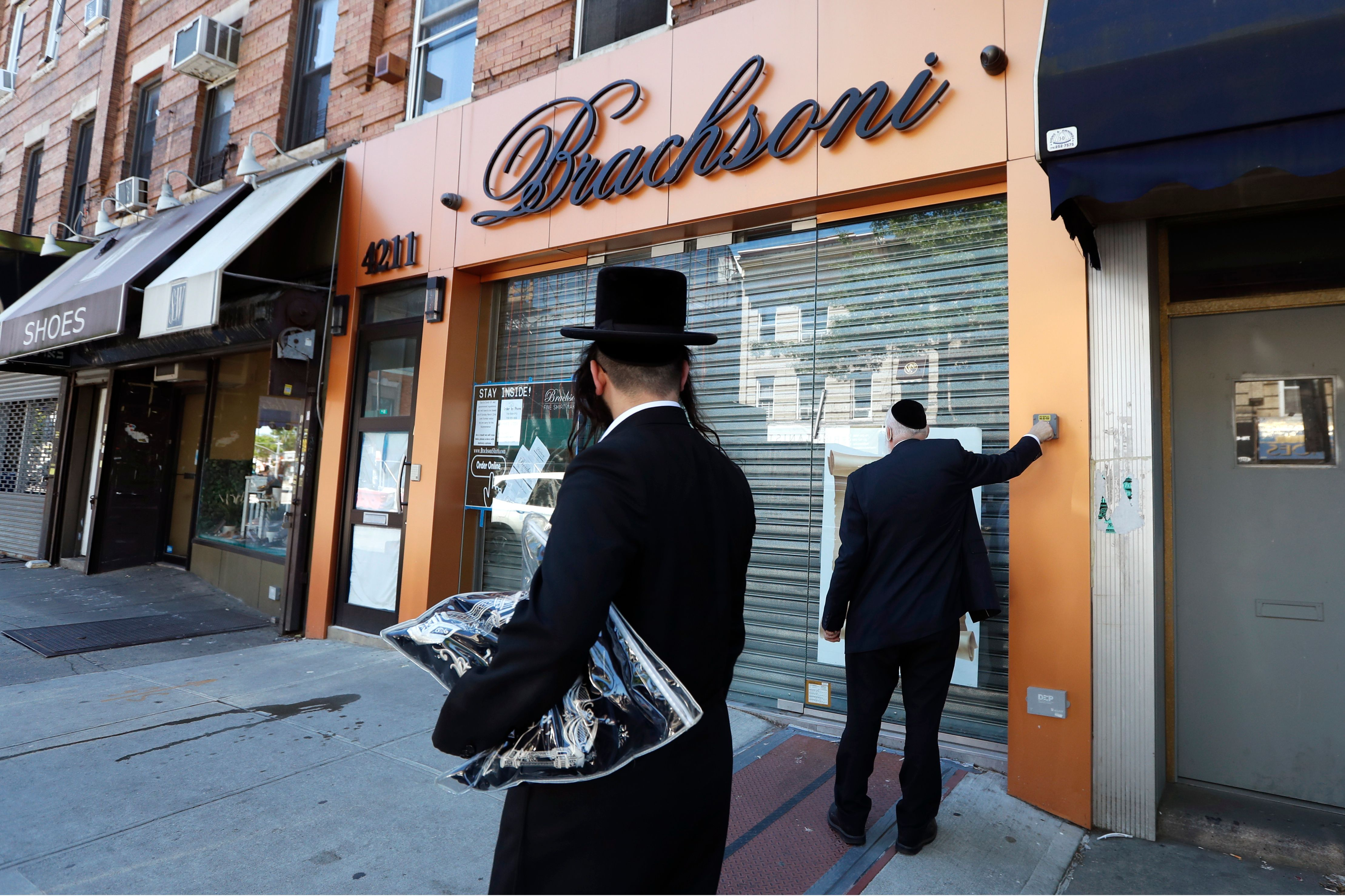 Pedestrian watches as Eli Brach, right, owner of Brachsoni, which specializes in the sale of men's white shirts, raises the protective shutter on his store, in Borough Park.
