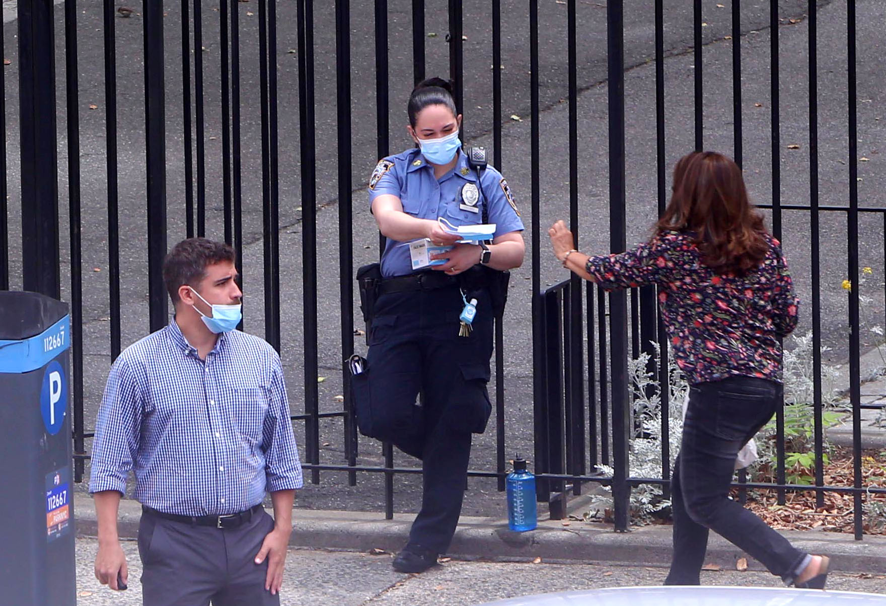 An NYPD officer in a mask hands out masks to people outside an Upper West Side Park. One man in the foreground has the mask under his nose.