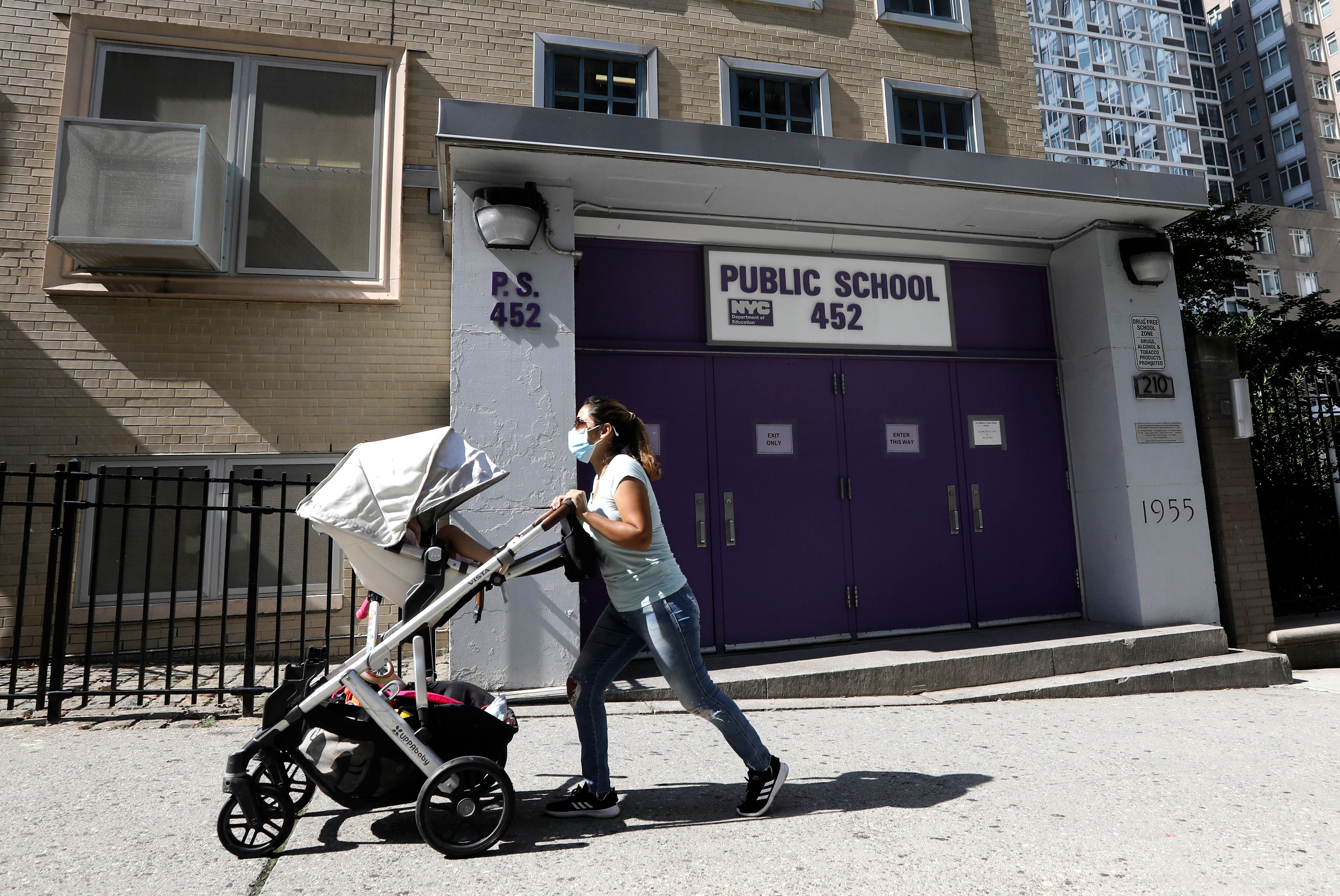 A woman pushes a baby stroller past Public School 452 in New York.
