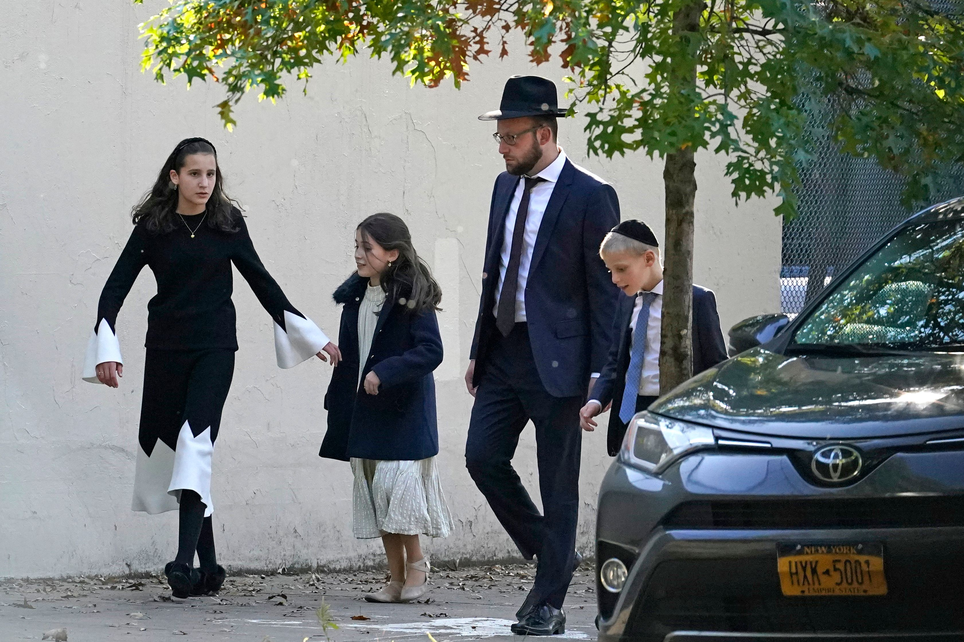 A man and his three children walk in Borough Park—no one is wearing masks.