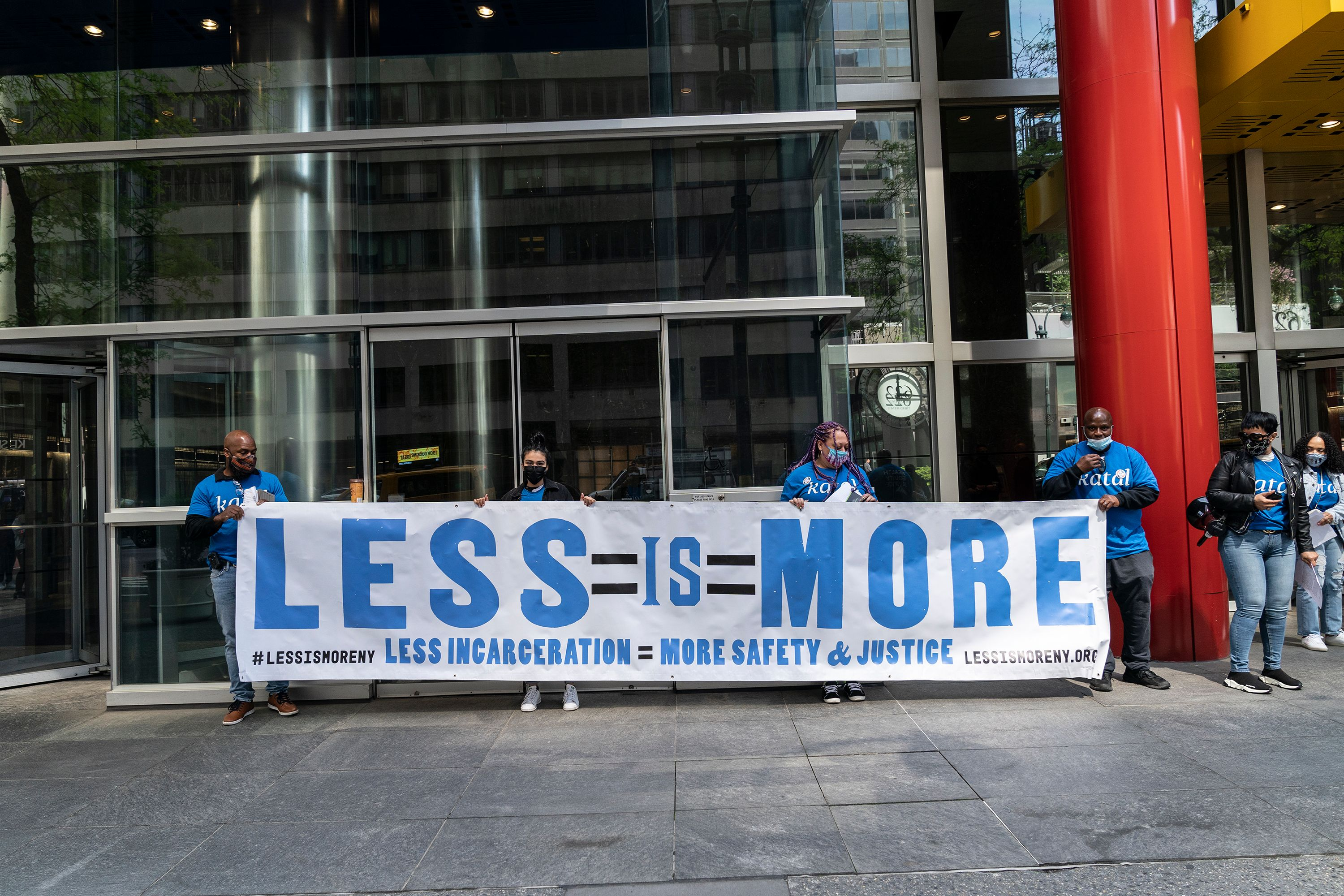 """A group of people with a banner that says """"Less in More"""" stands in front of a midtown Manhattan office building on the sidewalk"""