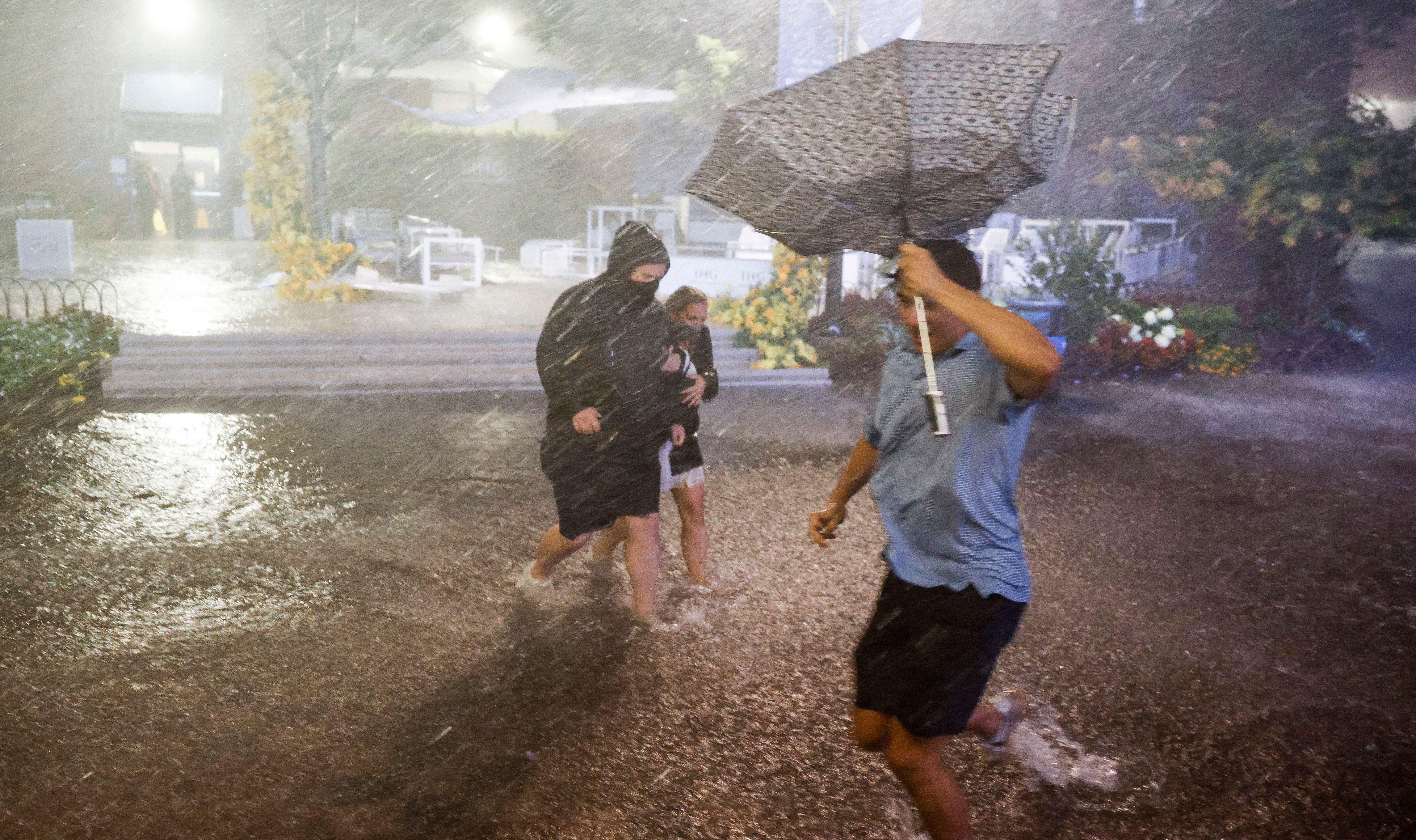 People navigate heavy rains and flooded walkways at the Billie Jean King National Tennis Center as the remnants of Hurricane Ida hit the area.