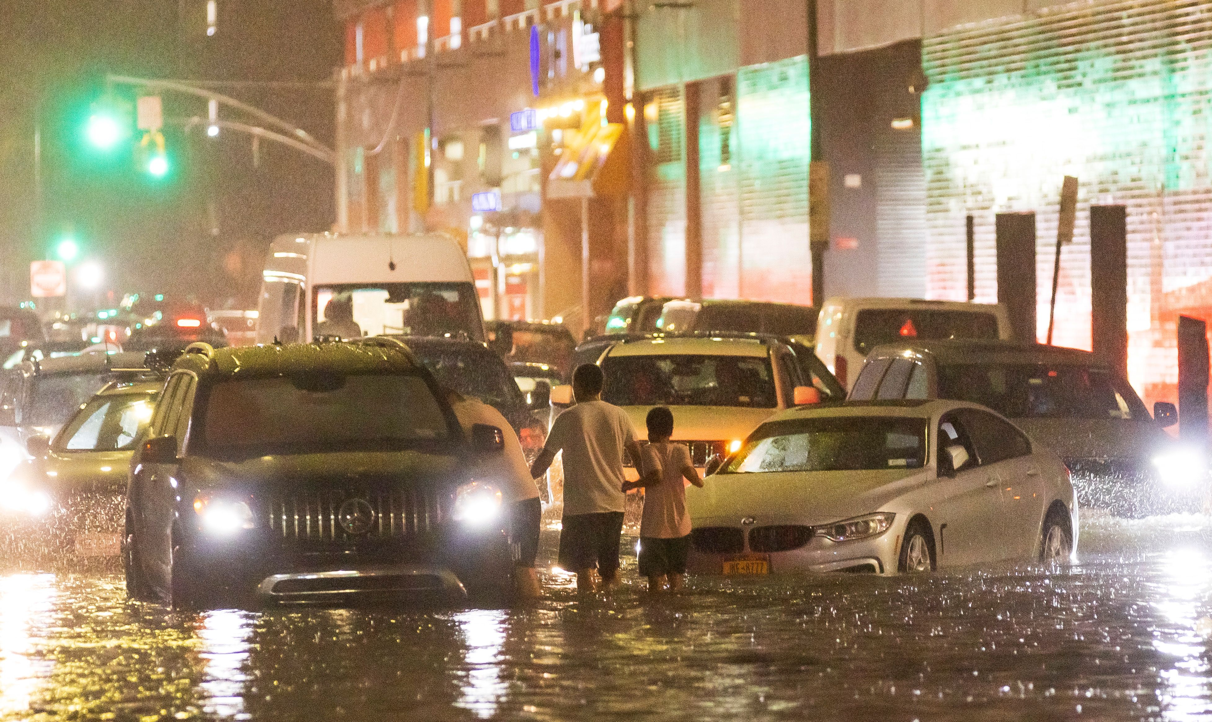 Vehicles stopped in flooded streets, an adult and a child stood in the middle of the street