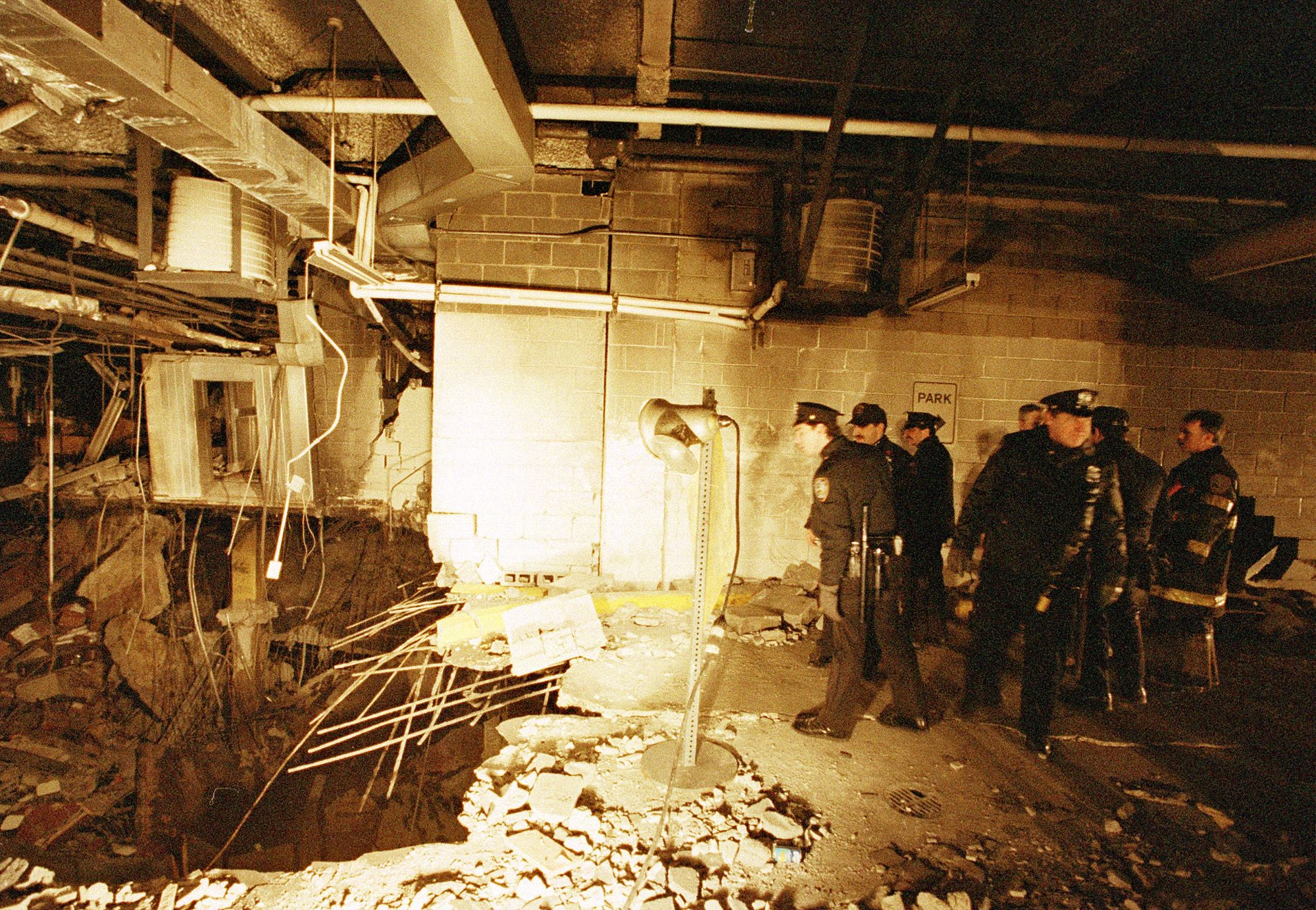 POlice officers and firefighters look at a huge crater in the parking garage